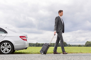 Full length side view of young businessman with suitcase leaving broken down car at countrysideの写真素材 [FYI03651321]