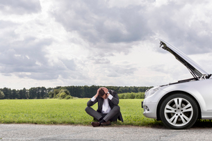 Full length of businessman with hands on head sitting by broken down car at countrysideの写真素材 [FYI03651322]