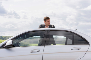 Young businessman leaning on broken down car at countrysideの写真素材 [FYI03651325]
