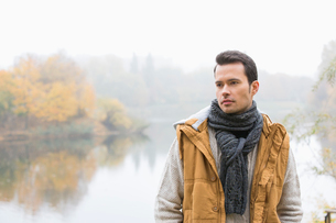 Thoughtful young man in warm clothing standing against lakeの写真素材 [FYI03651343]
