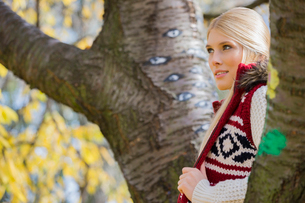 Thoughtful young woman in warm clothing standing near trees in parkの写真素材 [FYI03651366]
