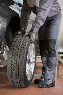 Low section of repairman fixing car's tire in workshopの写真素材 [FYI03651376]