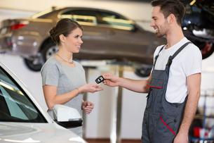 Happy repairman giving car key to woman in workshopの写真素材 [FYI03651380]