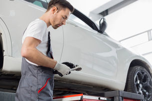 Side view of repairman holding tool while standing by car in workshopの写真素材 [FYI03651381]