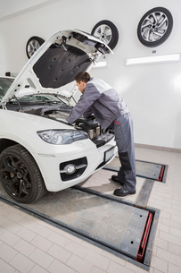 Full length side view of male automobile mechanic repairing car engine in repair shopの写真素材 [FYI03651391]