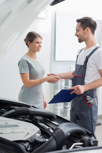 Young repair worker shaking hands with customer in car workshopの写真素材 [FYI03651395]