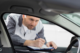 Male mechanic with clipboard checking car's interior in repair shopの写真素材 [FYI03651406]