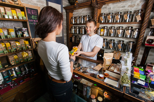 Salesperson giving product to female customer in tea storeの写真素材 [FYI03651430]