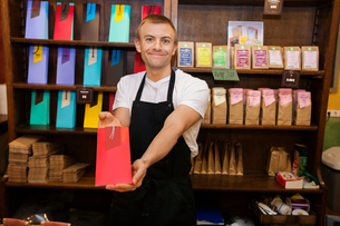 Portrait of male salesperson showing product in coffee storeの写真素材 [FYI03651437]