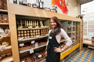 Portrait of confident saleswoman standing in supermarketの写真素材 [FYI03651438]