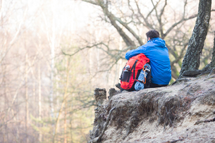 Rear view of hiker with backpack sitting on edge of cliff in forestの写真素材 [FYI03651467]
