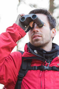 Young male backpacker using binoculars in forestの写真素材 [FYI03651472]