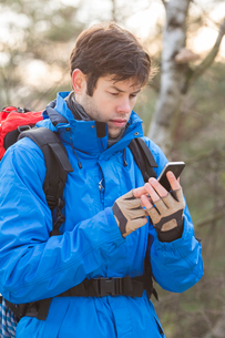 Young male hiker using smart phone in forestの写真素材 [FYI03651481]