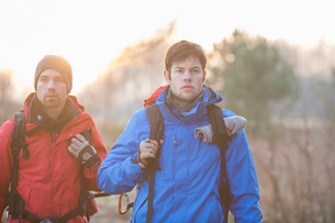 Young male hikers looking away in fieldの写真素材 [FYI03651484]