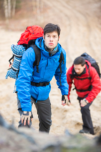 Young male backpackers hiking in forestの写真素材 [FYI03651494]