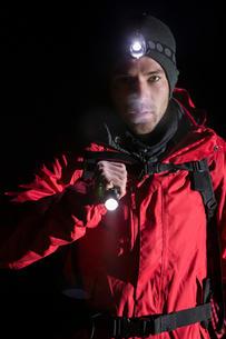 Portrait of confident male hiker with flashlight at nightの写真素材 [FYI03651512]