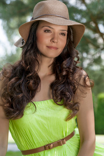 Portrait of trendy young woman wearing sunhat in parkの写真素材 [FYI03651522]