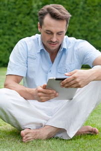 Full length of young man using digital tablet in parkの写真素材 [FYI03651540]