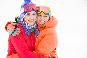 Portrait of happy young women in warm clothing embracing outdoorsの写真素材 [FYI03651579]