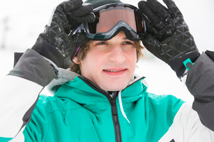 Handsome young man wearing ski goggles outdoorsの写真素材 [FYI03651587]