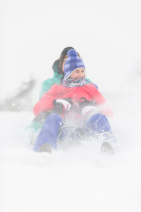 Cheerful young couple sledding in snowの写真素材 [FYI03651615]