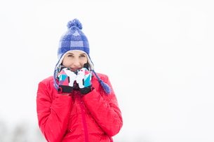 Beautiful young woman in warm clothing walking outdoorsの写真素材 [FYI03651616]