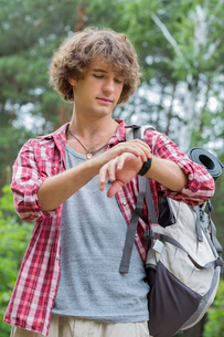 Young male hiker checking the time in forestの写真素材 [FYI03651630]