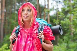 Beautiful backpacker in raincoat looking away at forestの写真素材 [FYI03651632]