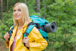 Smiling female backpacker in raincoat looking away at forestの写真素材 [FYI03651633]