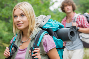 Beautiful female backpacker looking away with man in background at forestの写真素材 [FYI03651635]