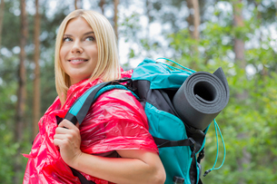 Side view smiling female backpacker in raincoat looking away at forestの写真素材 [FYI03651636]