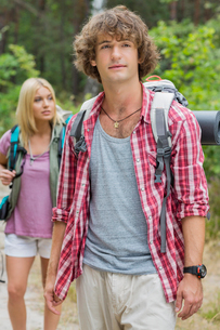 Male backpacker looking away with woman standing in background at forestの写真素材 [FYI03651637]