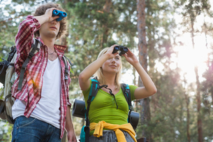 Hiking couple using binoculars in forestの写真素材 [FYI03651660]