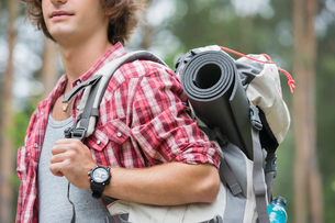 Midsection of male hiker carrying backpack in forestの写真素材 [FYI03651669]
