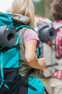 Rear view of female hiker carrying backpack with man in background outdoorsの写真素材 [FYI03651670]