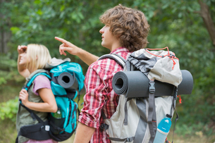 Male backpacker showing something to woman in forestの写真素材 [FYI03651671]