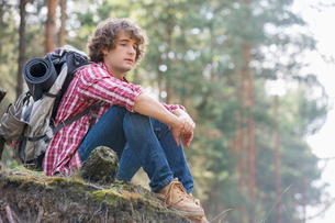 Full length of thoughtful male backpacker relaxing on cliff in forestの写真素材 [FYI03651682]