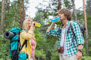 Young hiking couple drinking energy drinks in forestの写真素材 [FYI03651691]