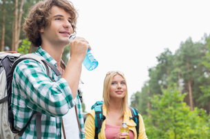 Hiking couple drinking energy drinks in forestの写真素材 [FYI03651696]