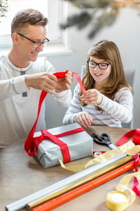 Happy father and daughter wrapping Christmas present at homeの写真素材 [FYI03651726]