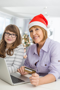 Portrait of mother and daughter shopping online during Christmasの写真素材 [FYI03651729]