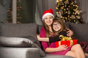 Happy girl hugging sister on sofa during Christmasの写真素材 [FYI03651735]