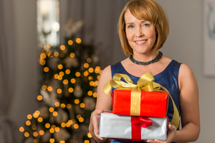 Portrait of smiling woman holding Christmas presents at homeの写真素材 [FYI03651743]