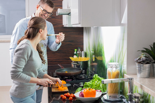 Happy man feeding food to woman cutting vegetables in kitchenの写真素材 [FYI03651757]
