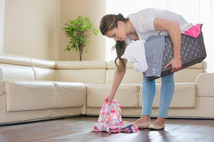 Woman with laundry basket picking clothes from floor in living roomの写真素材 [FYI03651768]