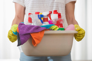 Midsection of woman carrying basket of cleaning suppliesの写真素材 [FYI03651769]