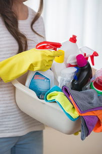 Midsection of woman carrying basket of cleaning supplies at homeの写真素材 [FYI03651772]