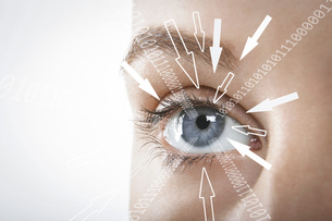 Cropped image of businesswoman with binary digits and arrow signs moving towards her eye against whiの写真素材 [FYI03651776]