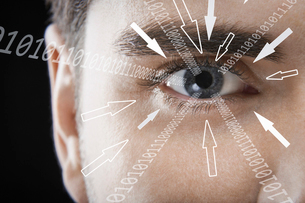Close-up portrait of businessman with binary digits and arrow signs moving towards his eye against bの写真素材 [FYI03651777]