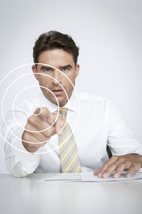 Portrait of serious businessman touching visual screen over white backgroundの写真素材 [FYI03651778]